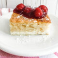 white cake on a white plate with cherry topping