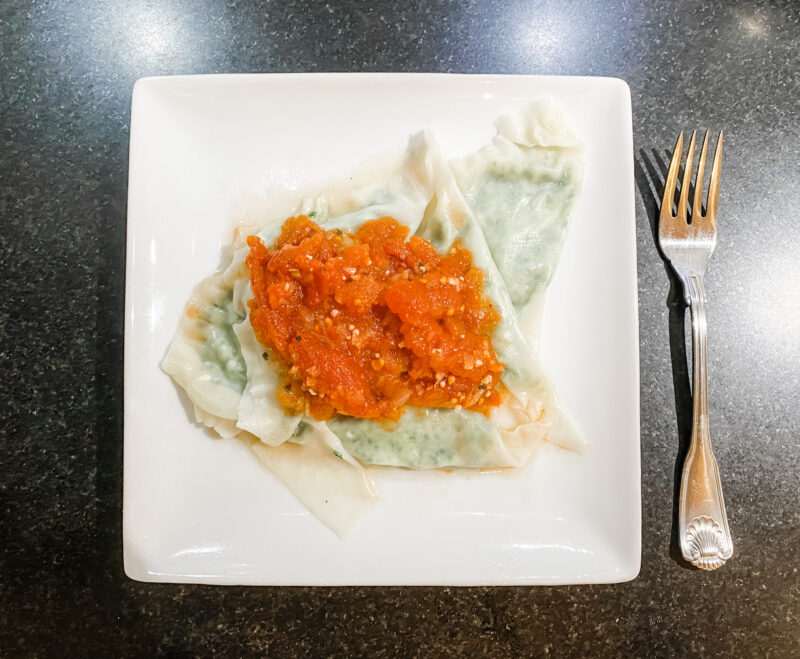 Homemade Spinach & Cheese Ravioli with tomato sauce on white square plate