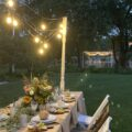 Al fresco Tablescape for fall with Edison light swag at dusk