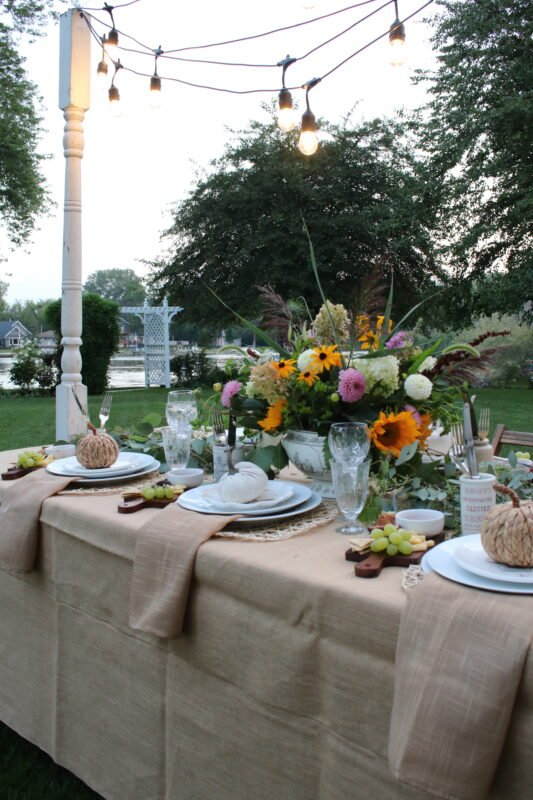 Fall Harvest Table set with fall inspired dishes and a beautiful floral centerpiece