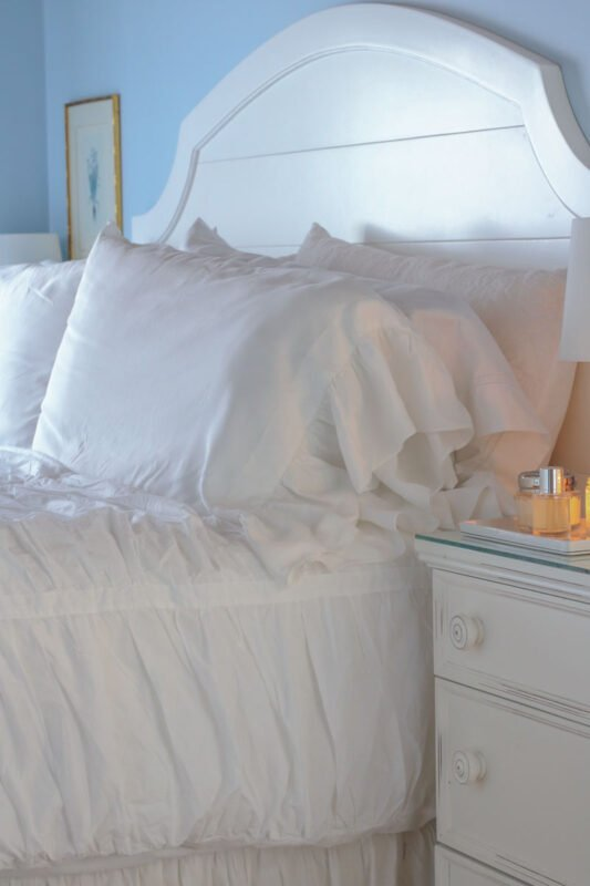 Lots of pillows and a duvet covered quilt on the bed