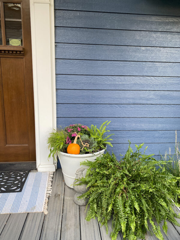 White pots with flowers on front porch next to the door with blue siding behind them