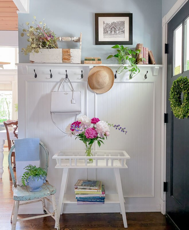 White headboard paneling with hooks for coats on a blue wall in a small entryway
