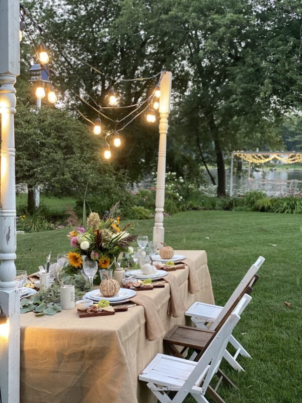 harvest tablescape with swagged Edison lights draped from vintage porch posts on either side of the table